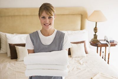 Maid holding towels in hotel room smiling