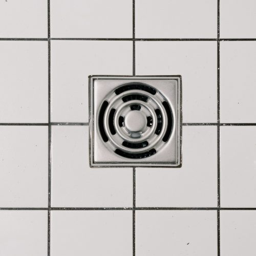 Tile and Grout Cleaning Gold Coast - close up of white tiles and a drain
