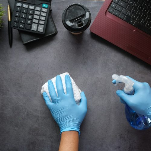 Office Cleaning Gold Coast - person wiping desk surface in office
